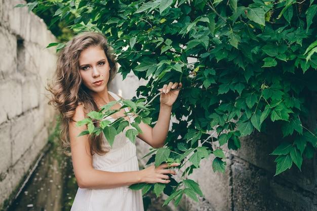 Belle fille heureuse aux cheveux naturels bouclés en robe blanche près des feuilles des arbres verts.
