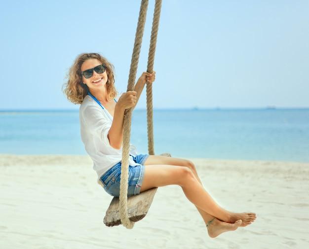 Belle fille heureuse sur une balançoire sur la plage. vacances, vacances, voyages