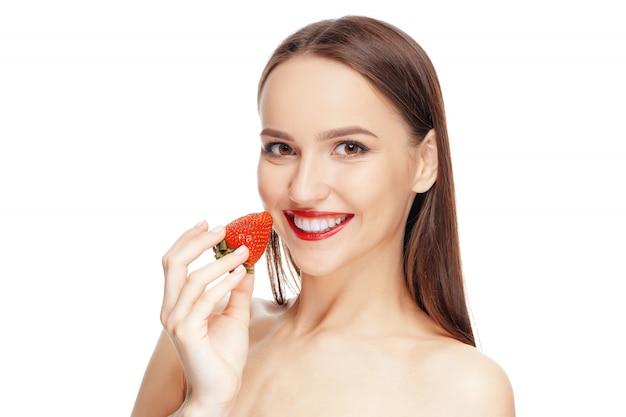 Belle fille heureuse avec une peau propre et fraîche, manger des fraises.