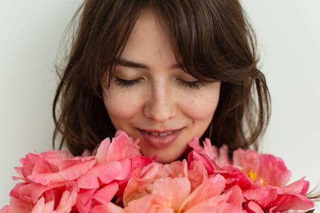 Belle fille heureuse souriante le jour de son anniversaire, visage d'une fille en gros plan avec des pivoines, saint valentin