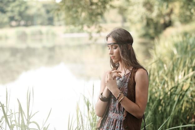 Belle fille hippie sur le fond d'un lac forestier