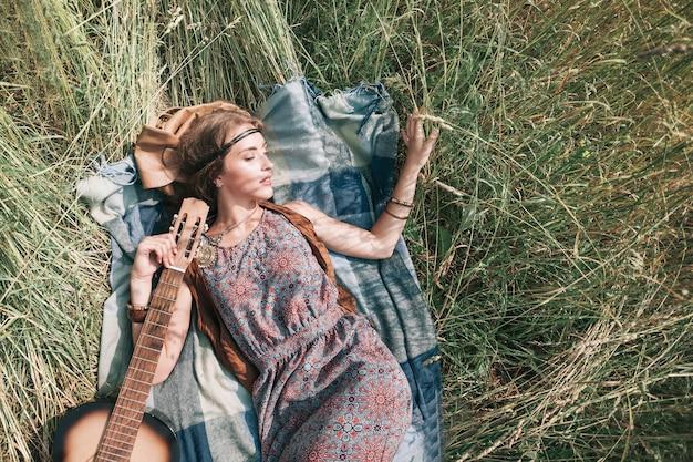 Belle fille hippie avec guitare couchée sur l'herbe tondue