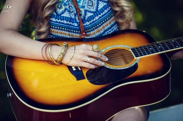 Belle fille hippie avec guitare dans le parc au coucher du soleil