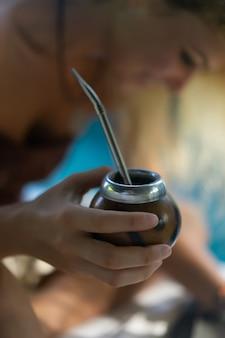 Belle fille hippie indienne aux longs cheveux blonds sur le toit, buvant du thé de son compagnon.