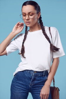 Belle fille hispanique charmante en t-shirt blanc, jeans et lunettes