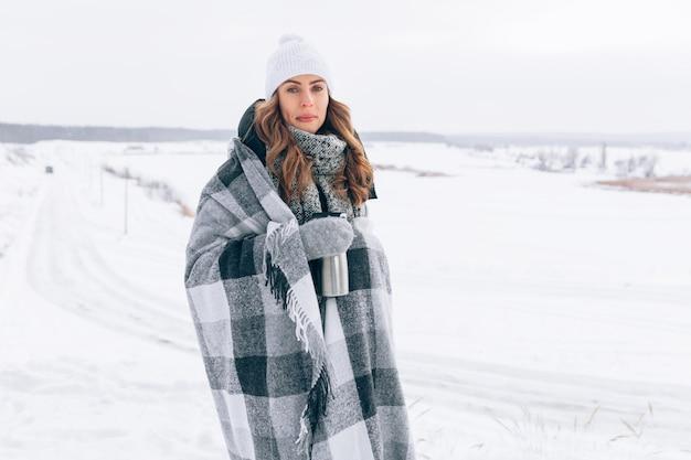 Belle fille en hiver recouverte d'un plaid avec une tasse de thermos et du thé chaud