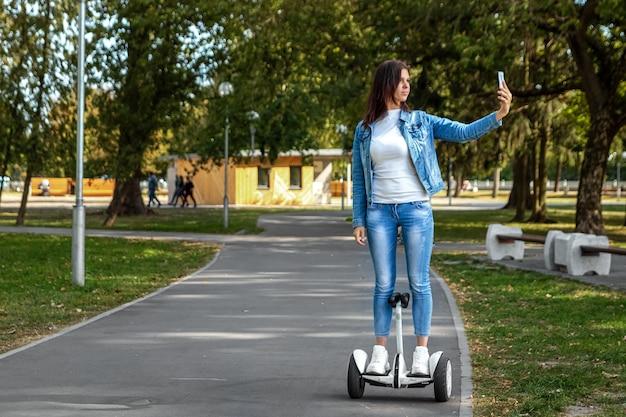 Belle fille sur un hoverboard blanc dans le parc
