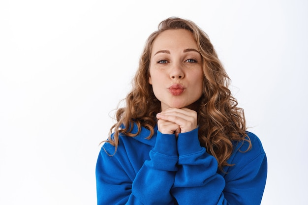 Belle fille idiote aux cheveux blonds bouclés, lèvres plissées, faisant un visage embrassant et une expression faciale mignonne, debout coquette sur un mur blanc