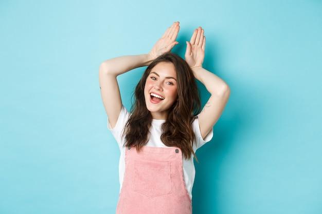 Belle fille imite le lapin de pâques, montrant des oreilles de lapin avec les mains sur la tête et souriant belle, dansant heureux, debout sur fond bleu