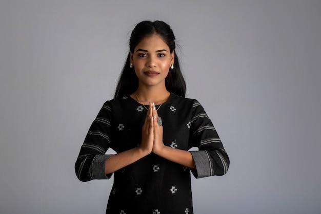 Belle fille indienne avec expression de bienvenue ou invitant ou saluant namaste