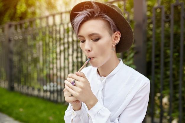Belle fille informelle avec les cheveux courts pourpre et dans un chapeau à la mode fume une cigarette de près