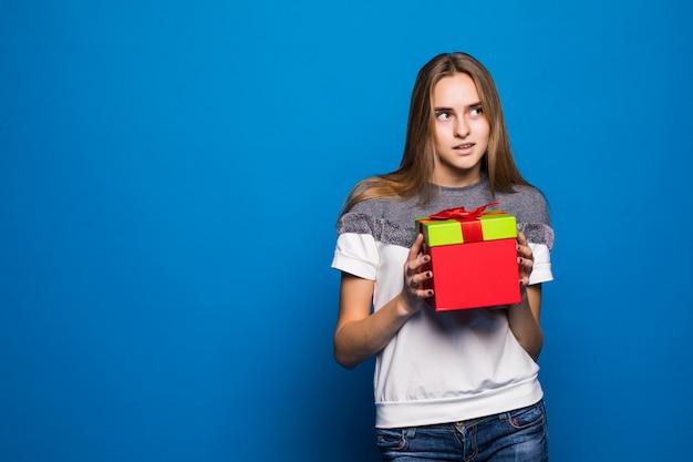 Belle fille intéressée veut ouvrir une boîte cadeau rouge