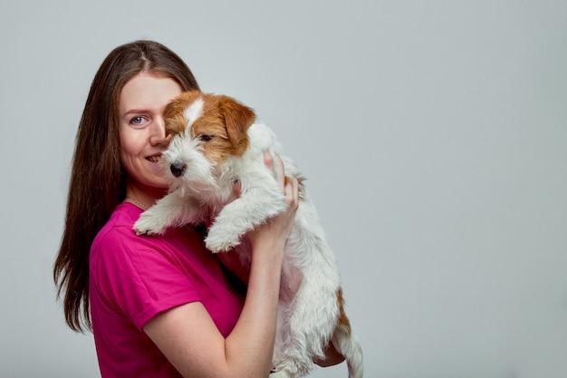 Belle fille avec un jack russell terrier sur ses mains sur un mur gris, copy space
