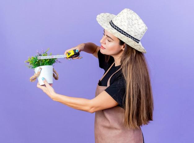 Belle fille de jardinier en uniforme portant chapeau de jardinage mesurant la fleur en pot de fleurs avec un ruban à mesurer isolé sur fond bleu