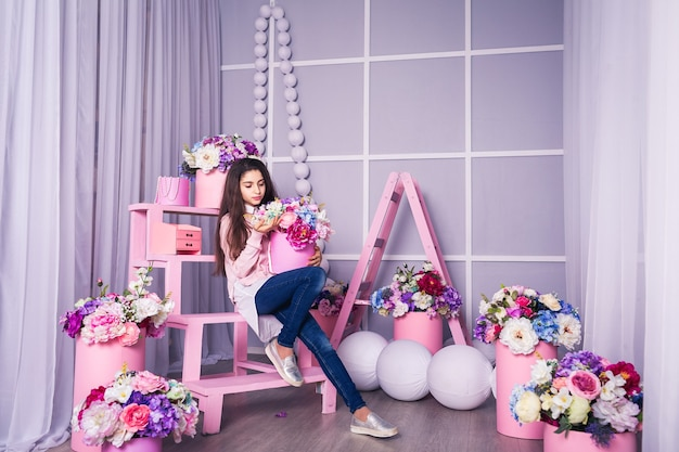Belle fille en jean et pull rose en studio avec décor de fleurs dans des paniers.