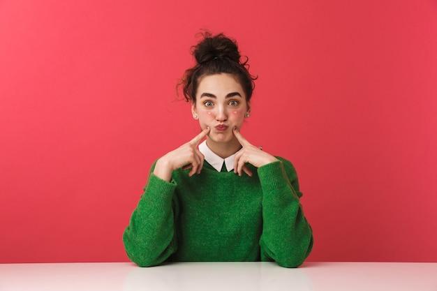 Belle fille jeune étudiante joyeuse assis à la table isolée