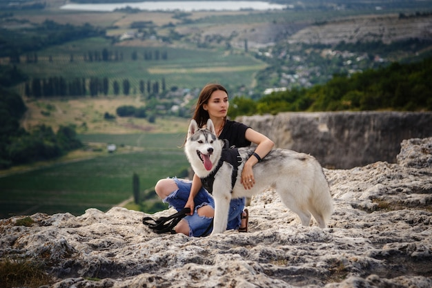 Belle fille joue avec un chien, husky gris et blanc, dans les montagnes au coucher du soleil. fille indienne et son loup