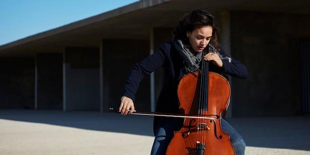 Belle fille joue du violoncelle avec passion dans un environnement concret