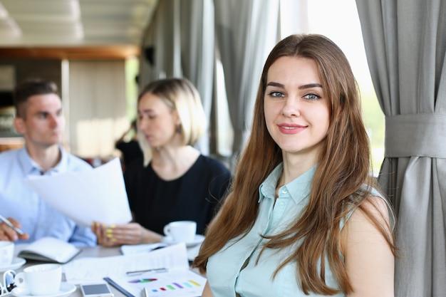 Belle fille joyeuse souriante au lieu de travail