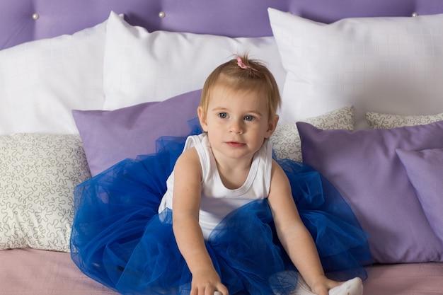 Belle fille en jupe princesse bleue est assise sur le lit