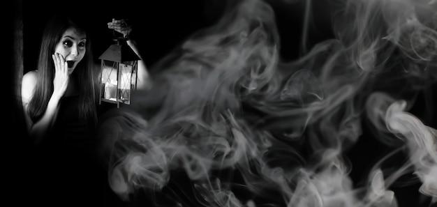 Belle fille avec une lanterne dans une pièce sombre en noir et blanc