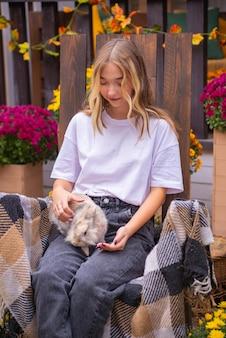 Belle fille avec un lapin à l'extérieur en automne près de la maison sur le banc