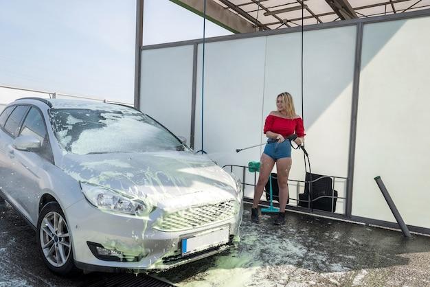Belle fille lave la mousse avec un pistolet à eau de sa voiture à la station de lavage de voiture en libre-service