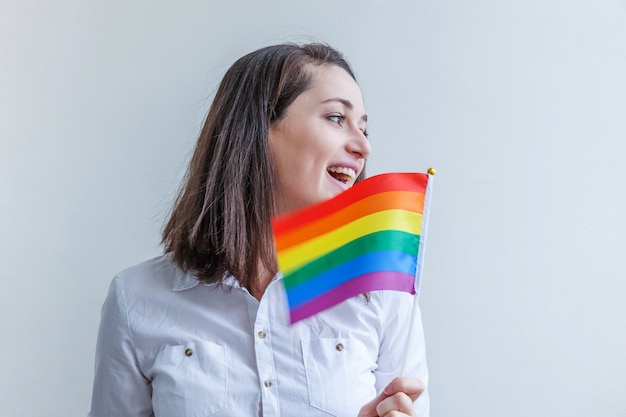 Belle fille lesbienne caucasienne avec drapeau arc-en-ciel lgbt isolé sur mur blanc à la recherche de plaisir et d'excitation. portrait de jeune femme gay pride. égalité des droits pour le concept de communauté lgbtq.