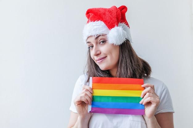Belle fille lesbienne en chapeau de père noël rouge avec drapeau arc-en-ciel lgbt isolé