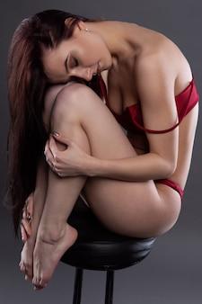 Une belle fille en lingerie sexy est assise sur une chaise avec sa tête sur ses genoux