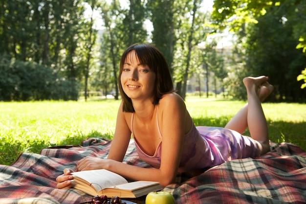 Belle fille lisant un livre en plein air
