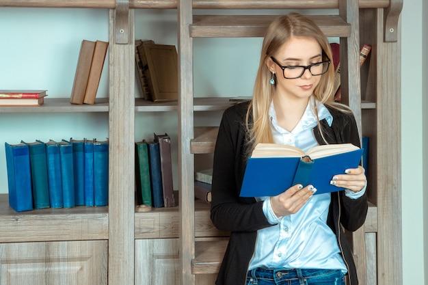 Belle fille avec des lunettes debout dans la bibliothèque à côté des étagères en bois de divers livres et lecture