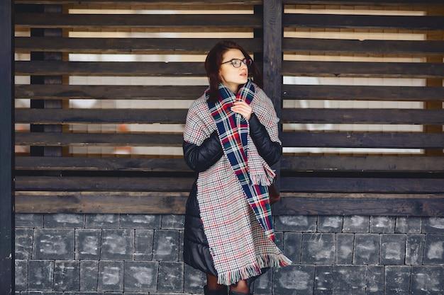 Belle fille à lunettes et une écharpe contre un mur en bois
