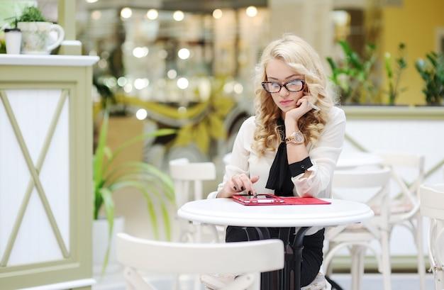 Belle fille à lunettes est assis à une table avec une tablette