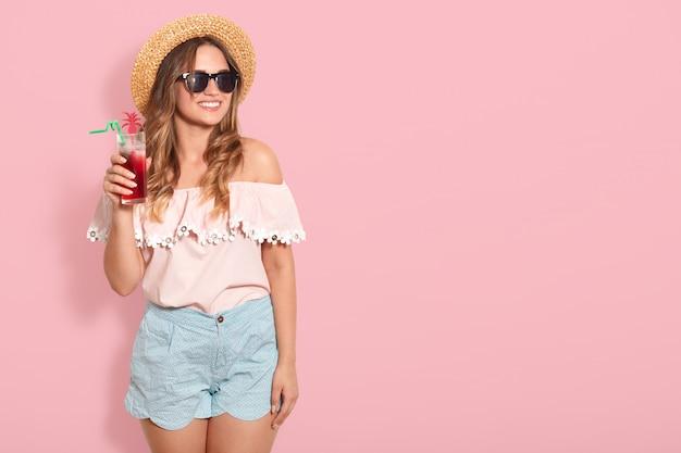 Belle fille à lunettes de soleil, chapeau de paille, chemisier d'été et cocktail d'été à boire court, regardant souriant de côté, posant isolé sur mur rose. copiez l'espace pour la publicité ou la promotion.
