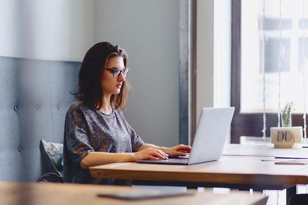 Une belle fille à lunettes travaille pour un ordinateur portable dans un café