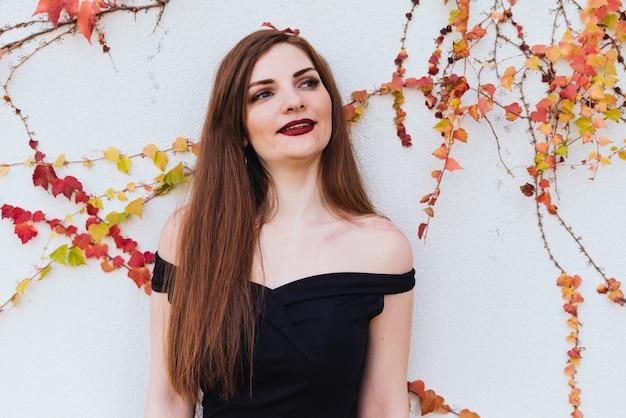 Belle fille magnifique aux cheveux longs dans une robe noire posant sur le mur, souriant, appréciant le reste