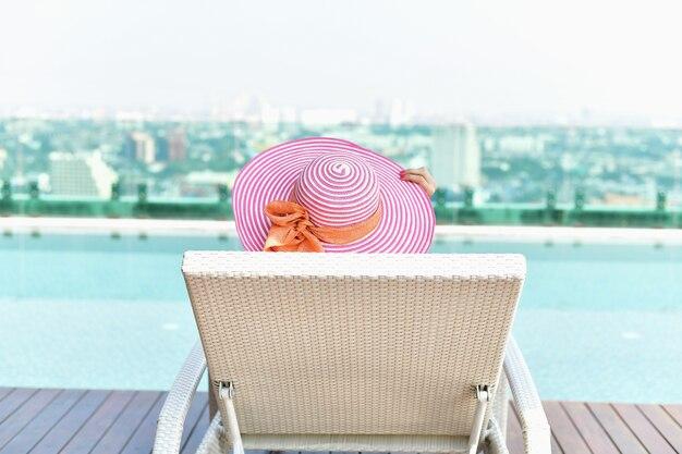 Belle fille en maillot de bain est relaxant à la piscine