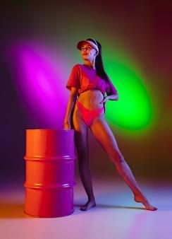 Belle fille en maillot de bain sur fond de studio néon