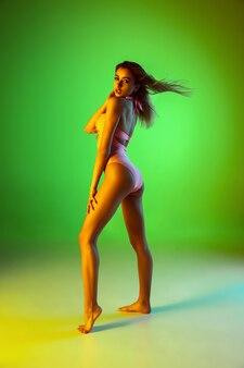 Belle fille en maillot de bain à la mode isolée sur fond de studio dégradé en été néon