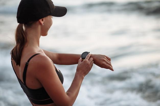 Belle fille en maillot de bain noir bénéficie d'une montre de sport intelligente au bord de la mer