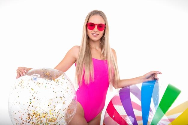 Une belle fille en maillot de bain rose et lunettes pose avec deux balles gonflables