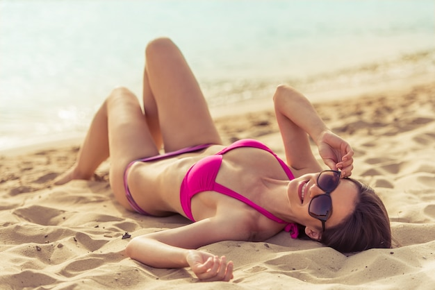 Belle fille en maillot de bain rose et lunettes de soleil.