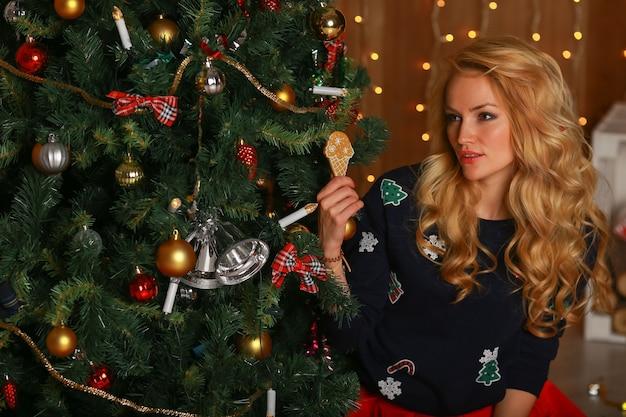 La belle fille avec des mains de biscuits s'assied près d'un arbre de noël