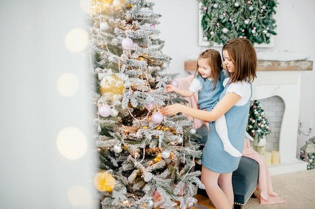 Belle fille avec maman décore le sapin de noël à la maison. famille heureuse. joyeux noel et bonne année.