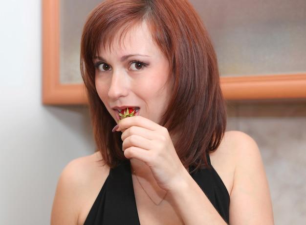 Une belle fille mange une fraise