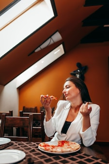 Belle fille mangeant une pizza au restaurant