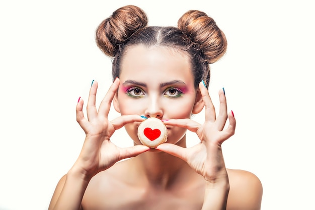 Belle fille de mannequin avec des biscuits sucrés avec des coeurs sur une surface blanche aime la saint-valentin