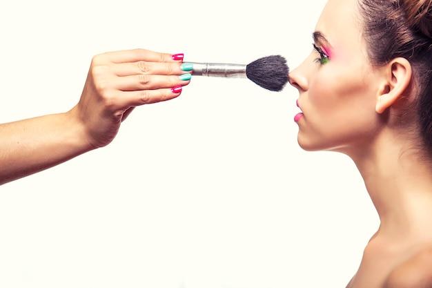 Belle fille mannequin dont le maquilleur applique le maquillage, la poudre et le fard à joues, sur une surface blanche