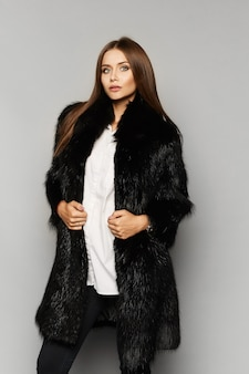 Belle fille de mannequin avec un maquillage parfait en manteau de fourrure de luxe, isolé sur le fond.